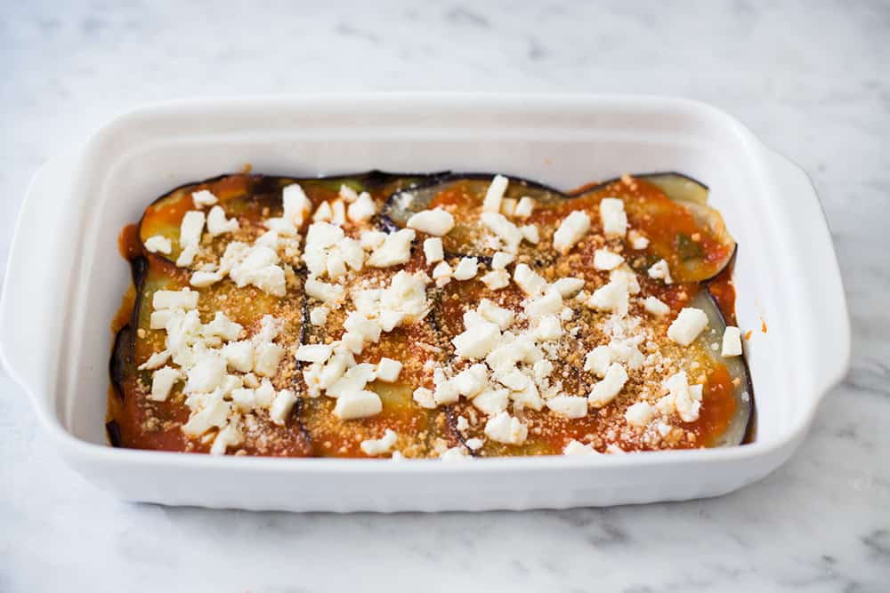 Eggplant parmigiana in a oven dish ready for baking.