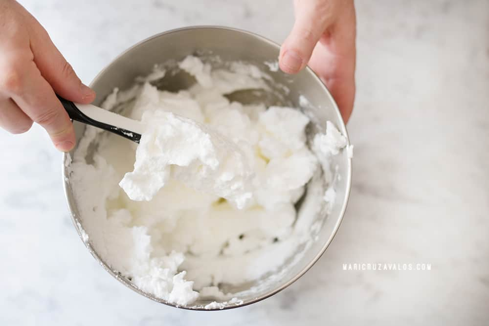 Showing egg whites mixed with syrup until stiff peaks.