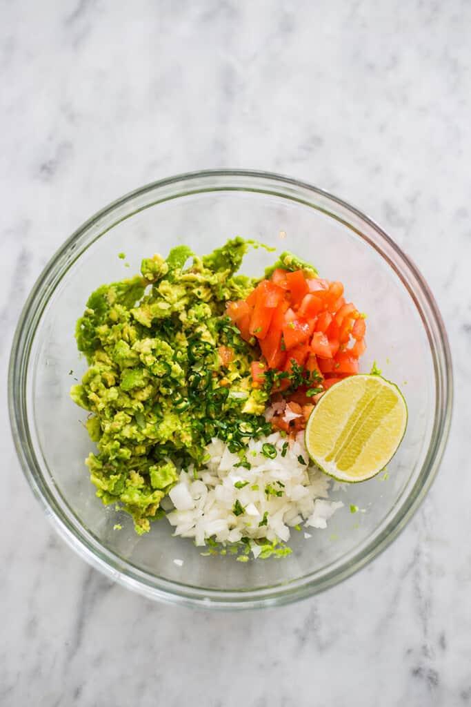 Come fare il guacamole messicano: Gli ingredienti prima di mescolare, dentro una ciotola.
