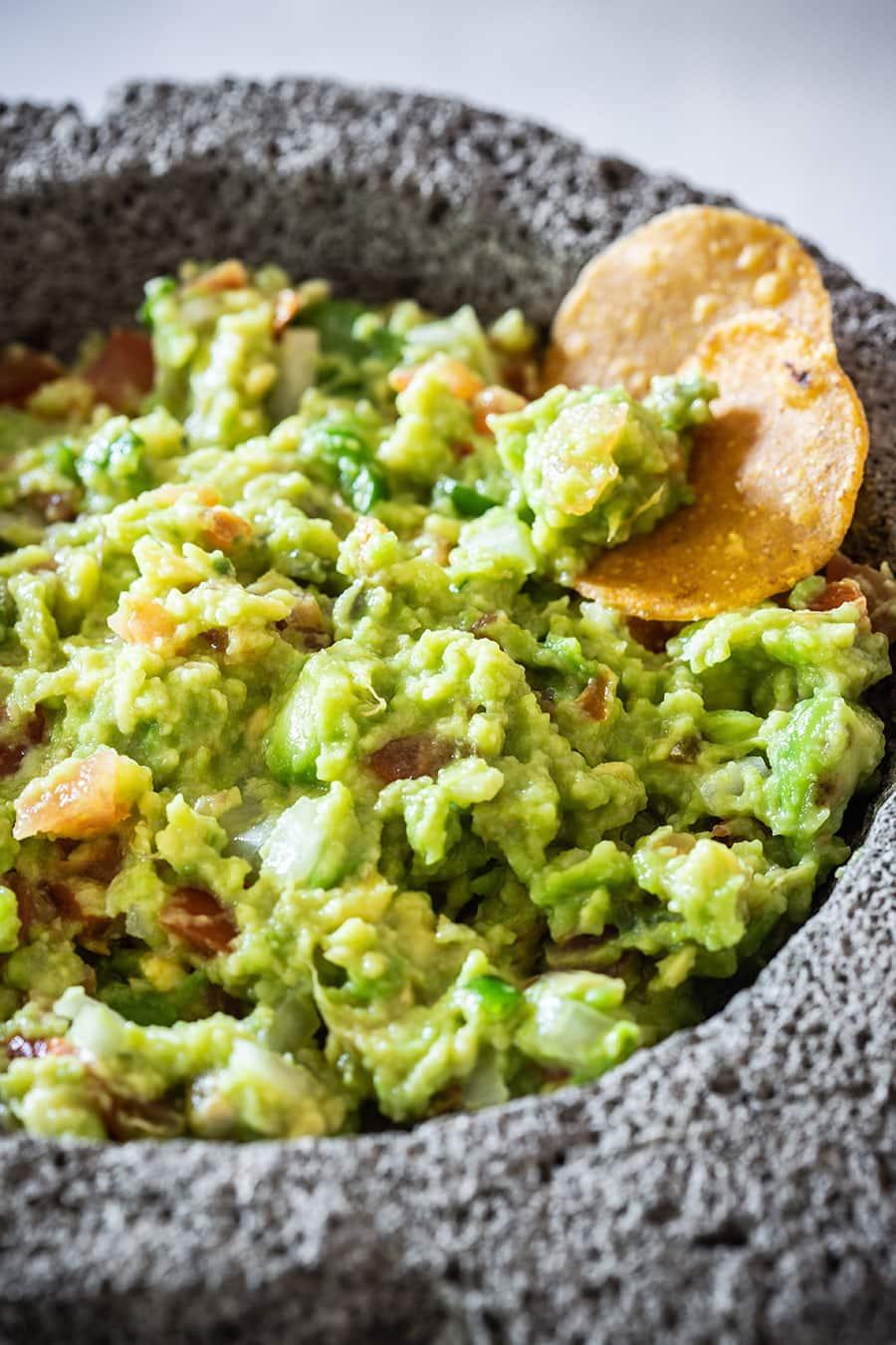 A close up of guacamole recipe on molcajete.