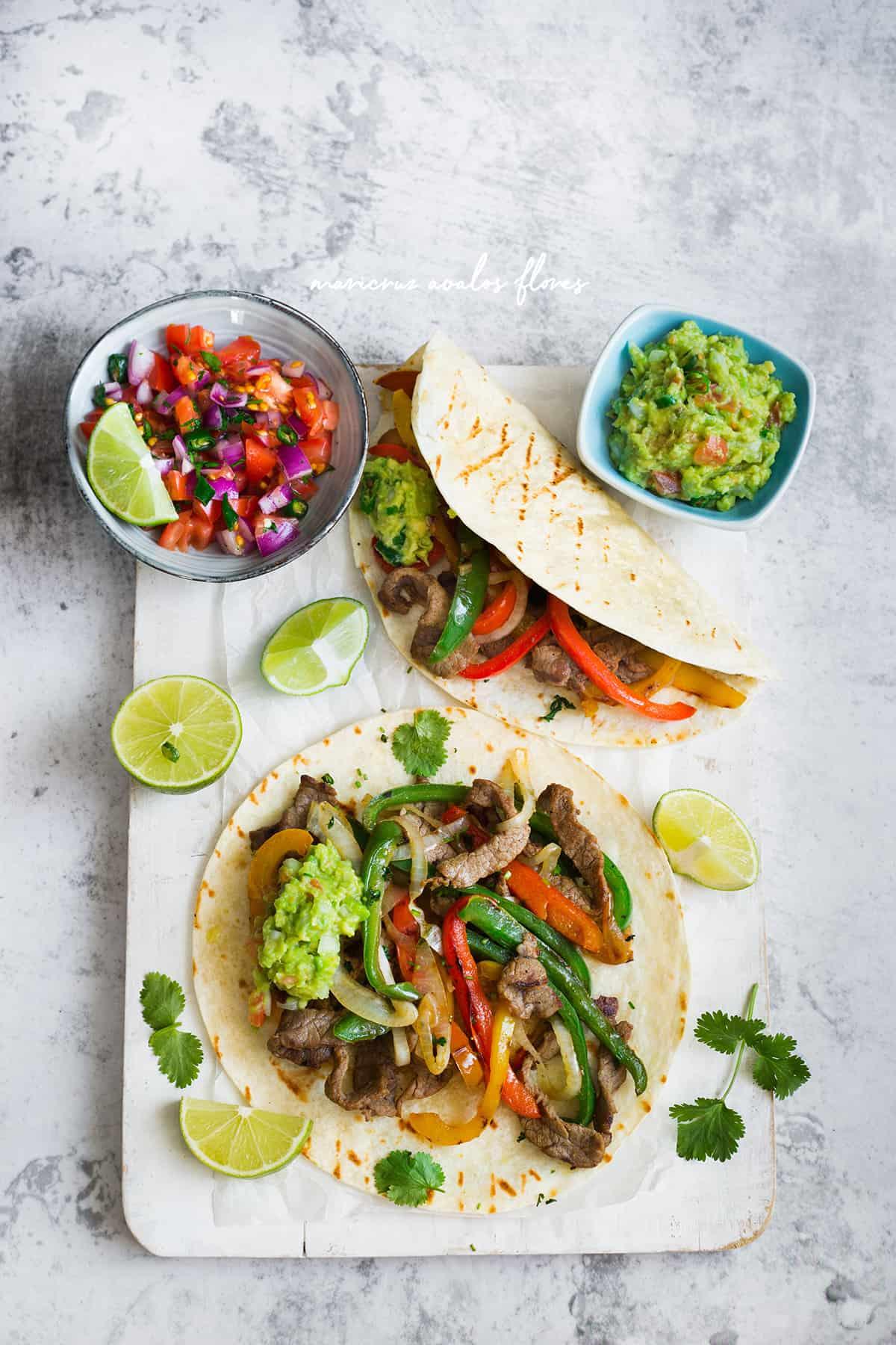 Foto desde arriba de las fajitas de res servidas en tortillas de harina con guacamole y pico de gallo.