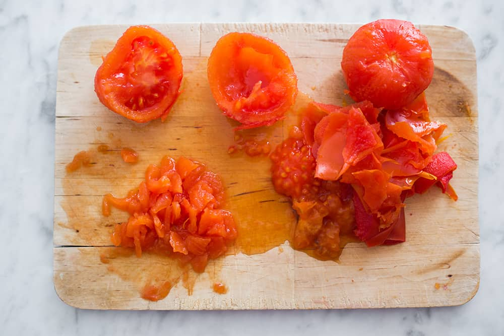Tomatoes boiled, peeled and cut into pieces on a cutting board.