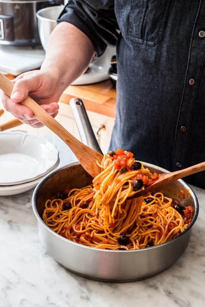 A man tossing spaghetti with vegan puttanesca sauce.