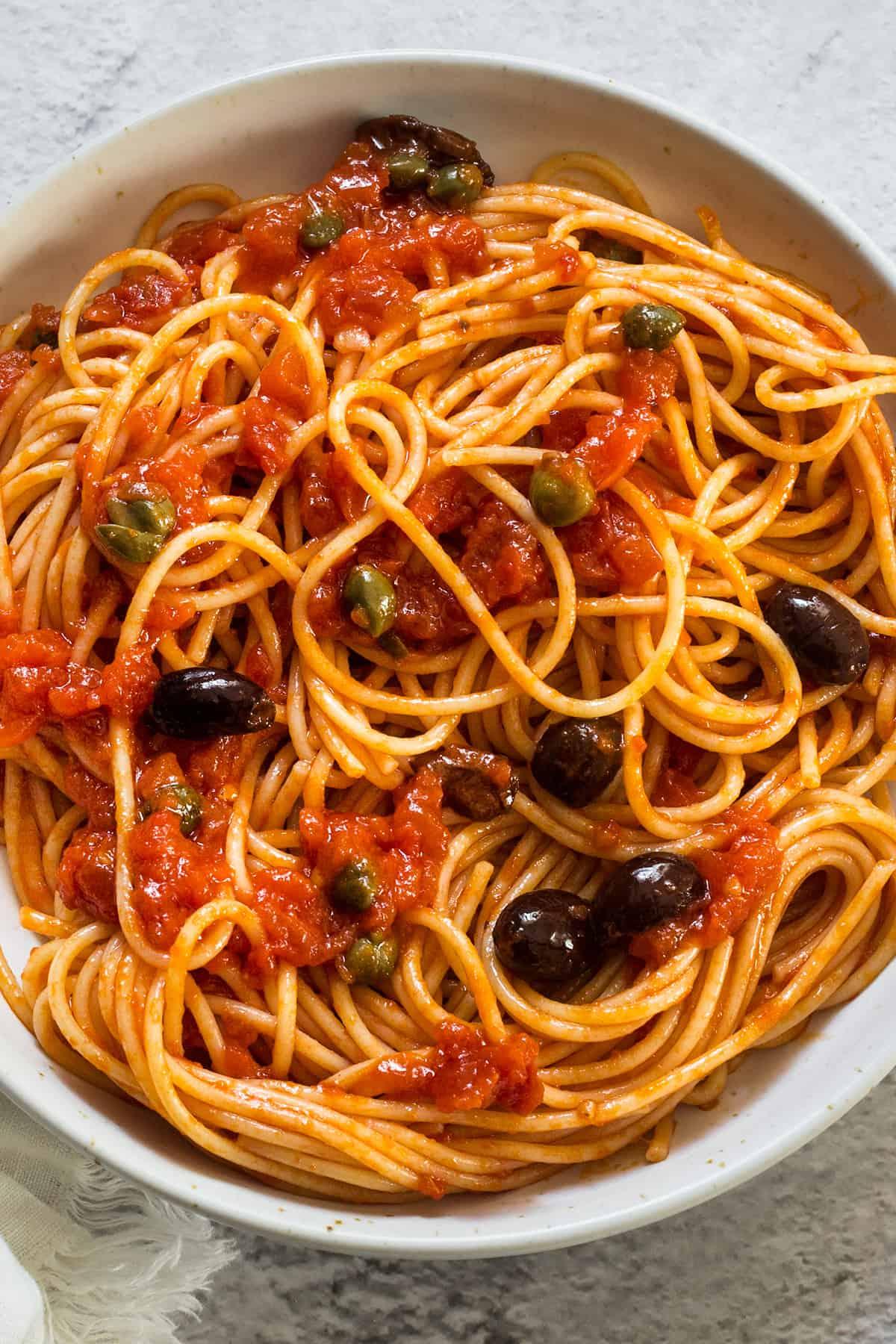 A close uo on a plate with spaghetti alla puttanesca.