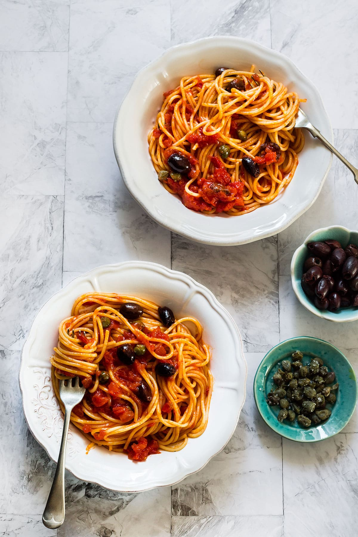 Two plates with spaghetti alla puttanesca seen from above.