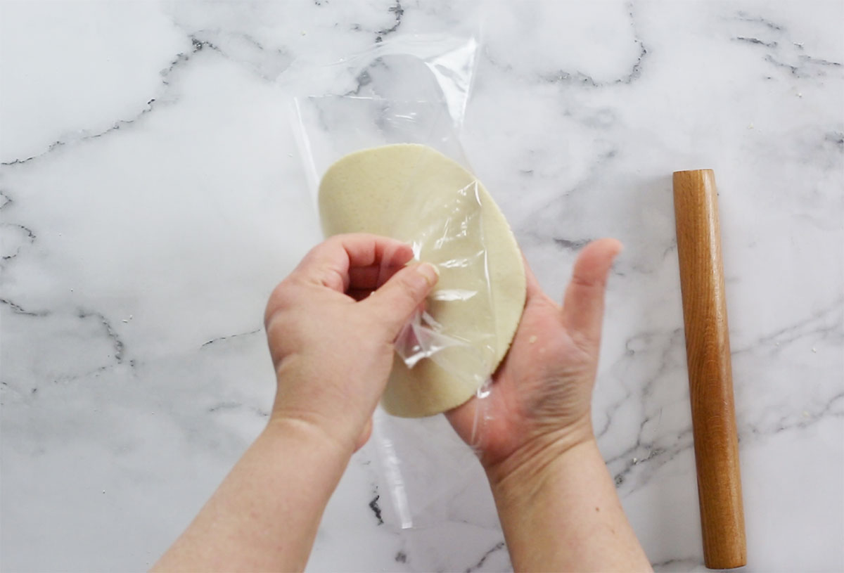 Tortilla placed on hand while peeling the sheet on top.