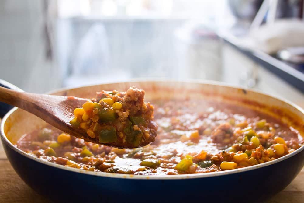 Una cuchara mostrando un poco de la carne preparada con salsa y verduras.