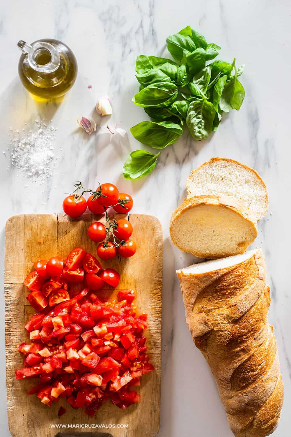 Ingredients for bruschetta al pomodoro displayed on a marble surface.