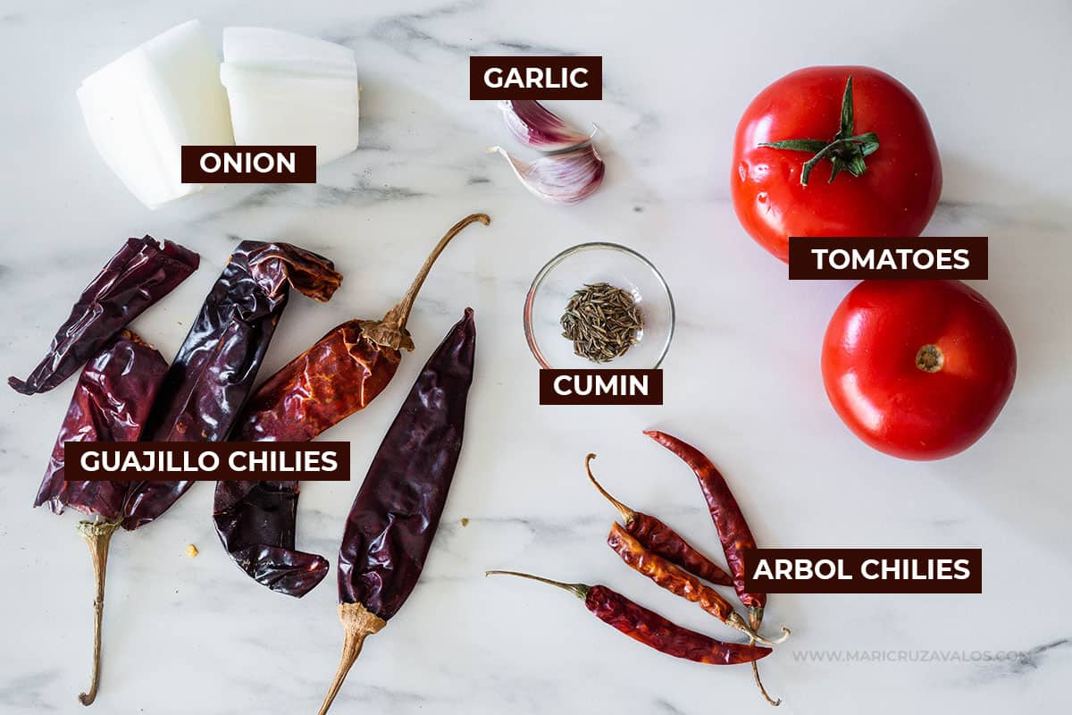 All ingredients for the salsa displayed on a marble surface.
