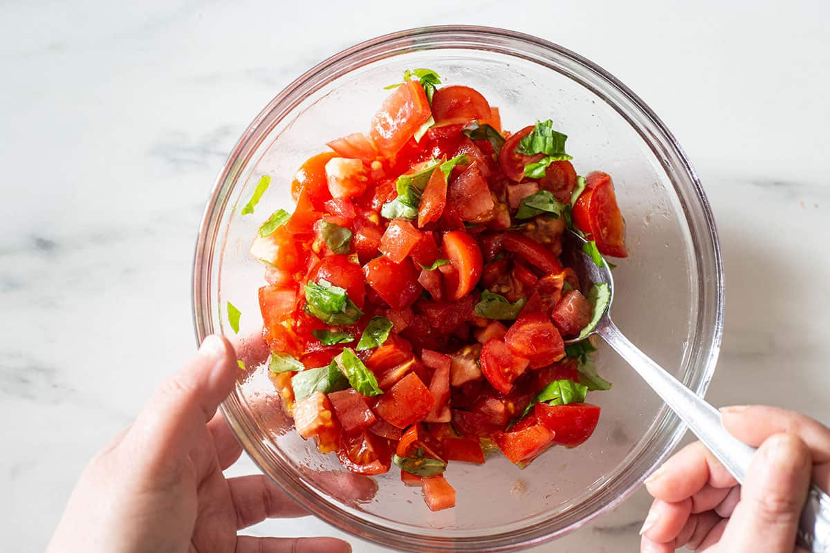 Mixing tomatoes on a bowl.