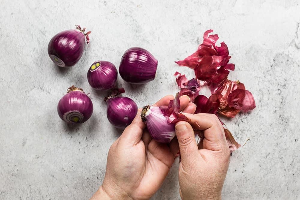 Peeling red onions.