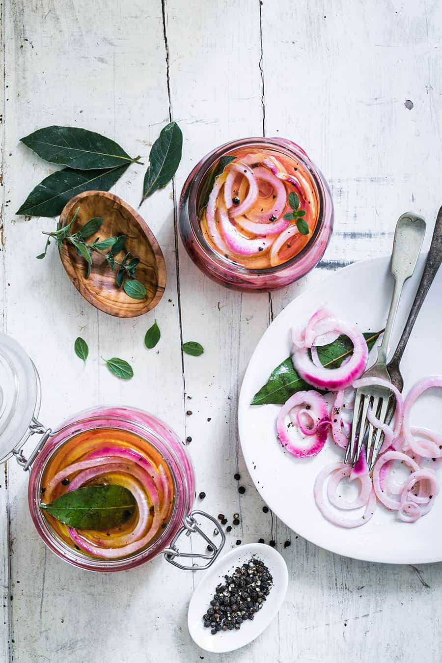 Two jars with red pickled onions made with peppercorns, bay leaves and marjoram.