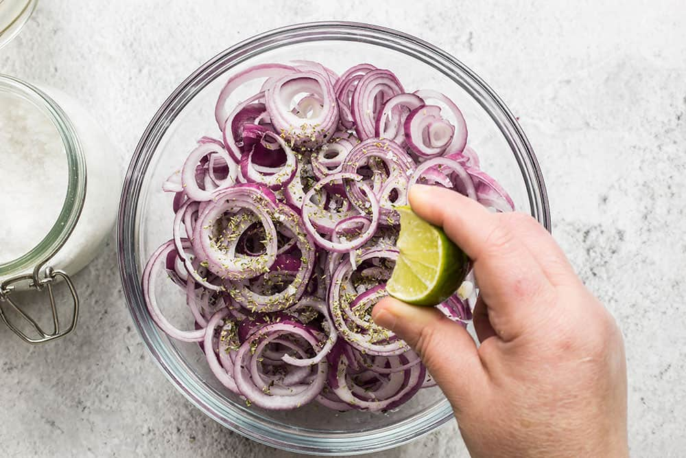 Squeezing lemon on top of sliced onions on a bowl.