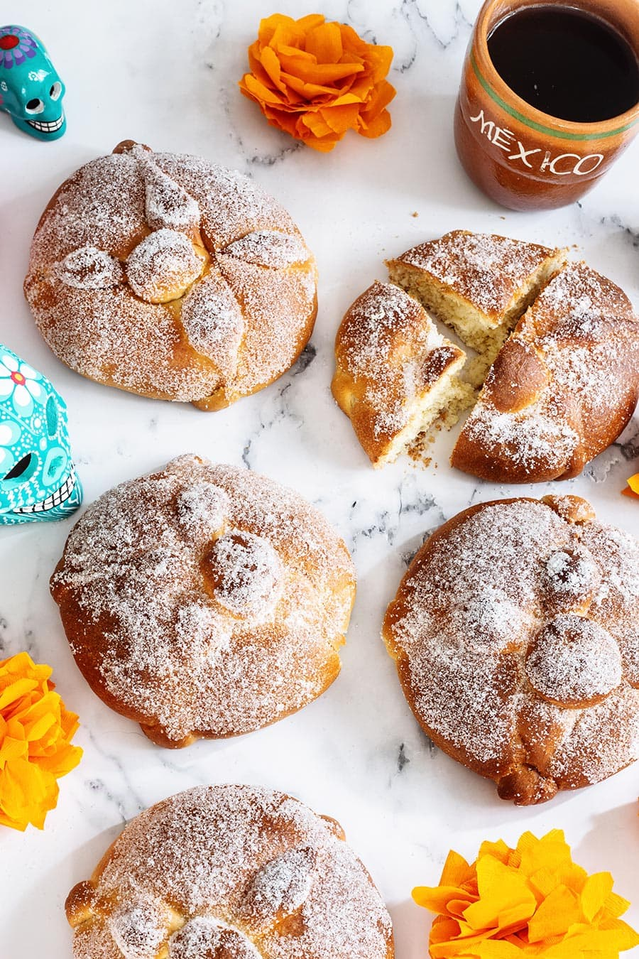 Bread of the dead, a.k.a pan de muerto displayed on a marble surface.