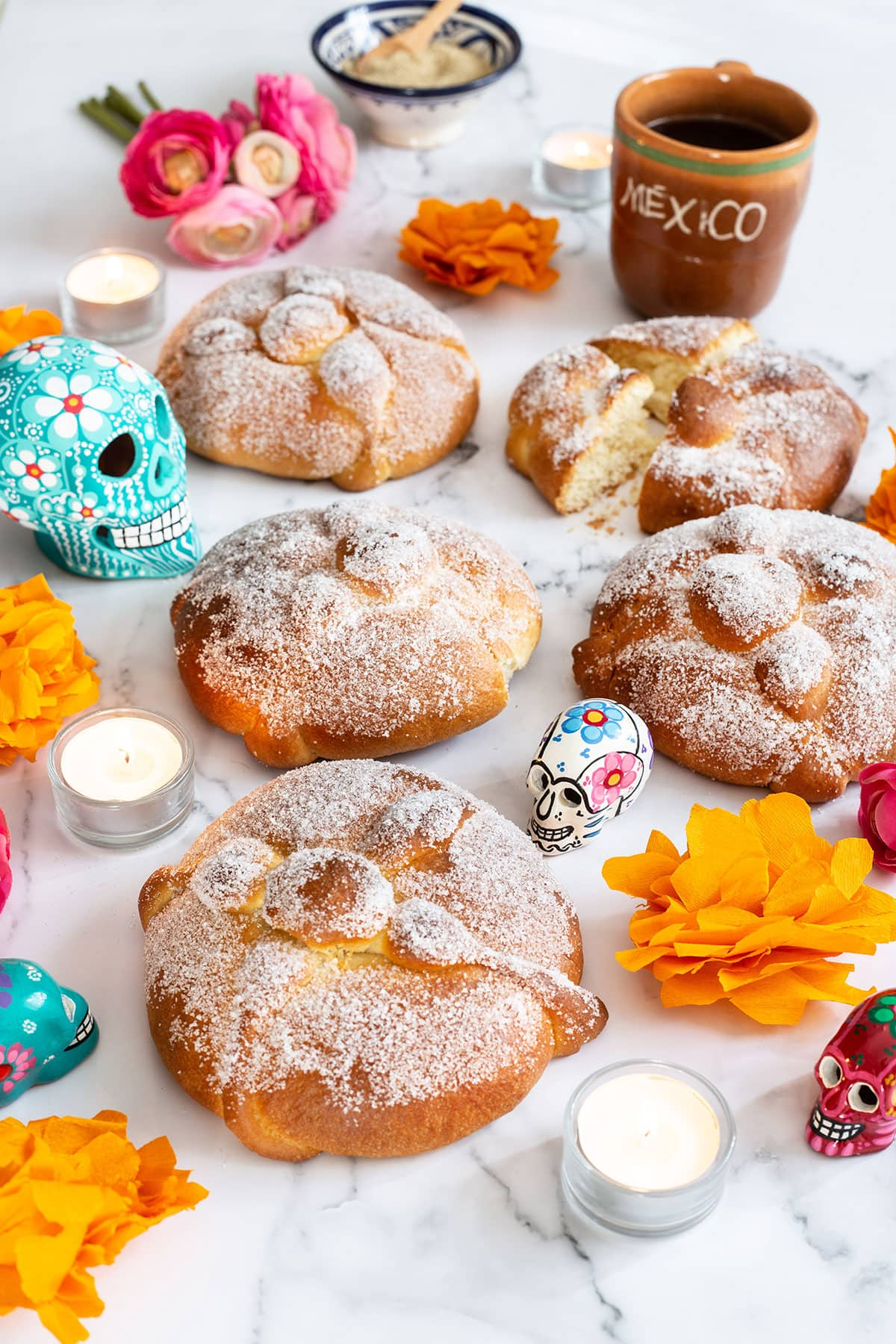 Mexican pan de muerto displayed with various decorations.