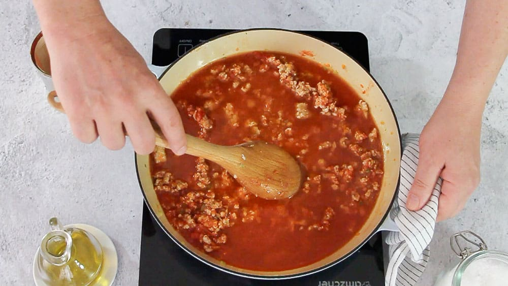Mixing meat with tomato sauce.