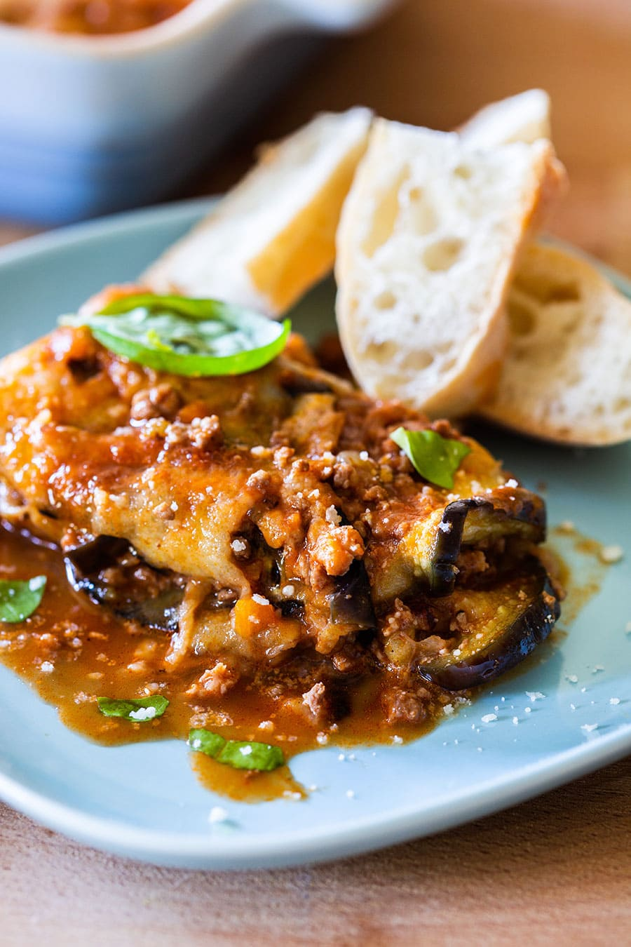 Eggplant lasagna served on a blue plate with some bread slices on the side.