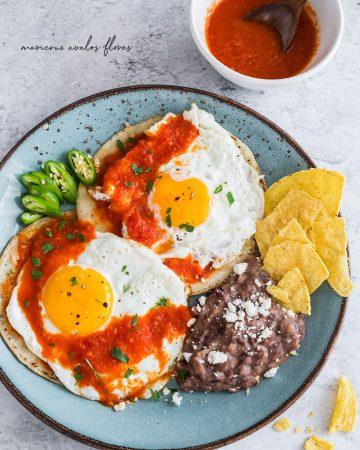 un piatto di huevos rancheros servito con fagioli e tortillas