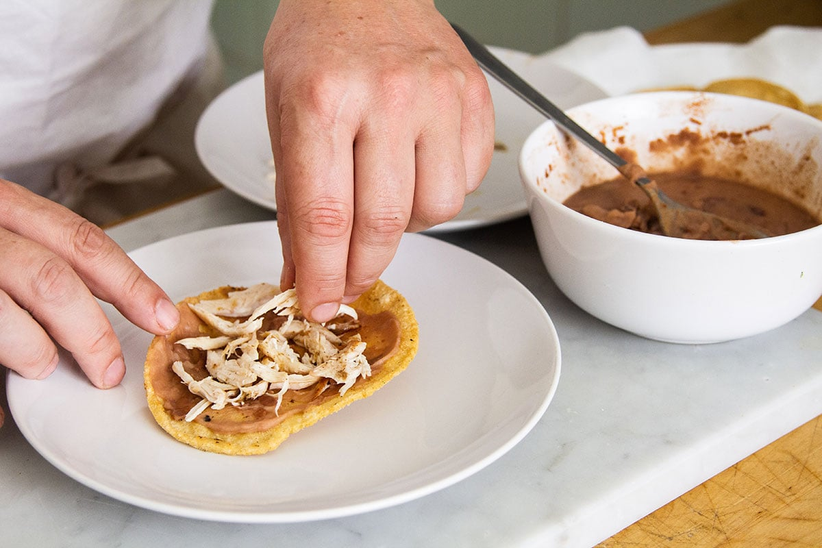 Adding chicken on top of mashed beans on a tostada.
