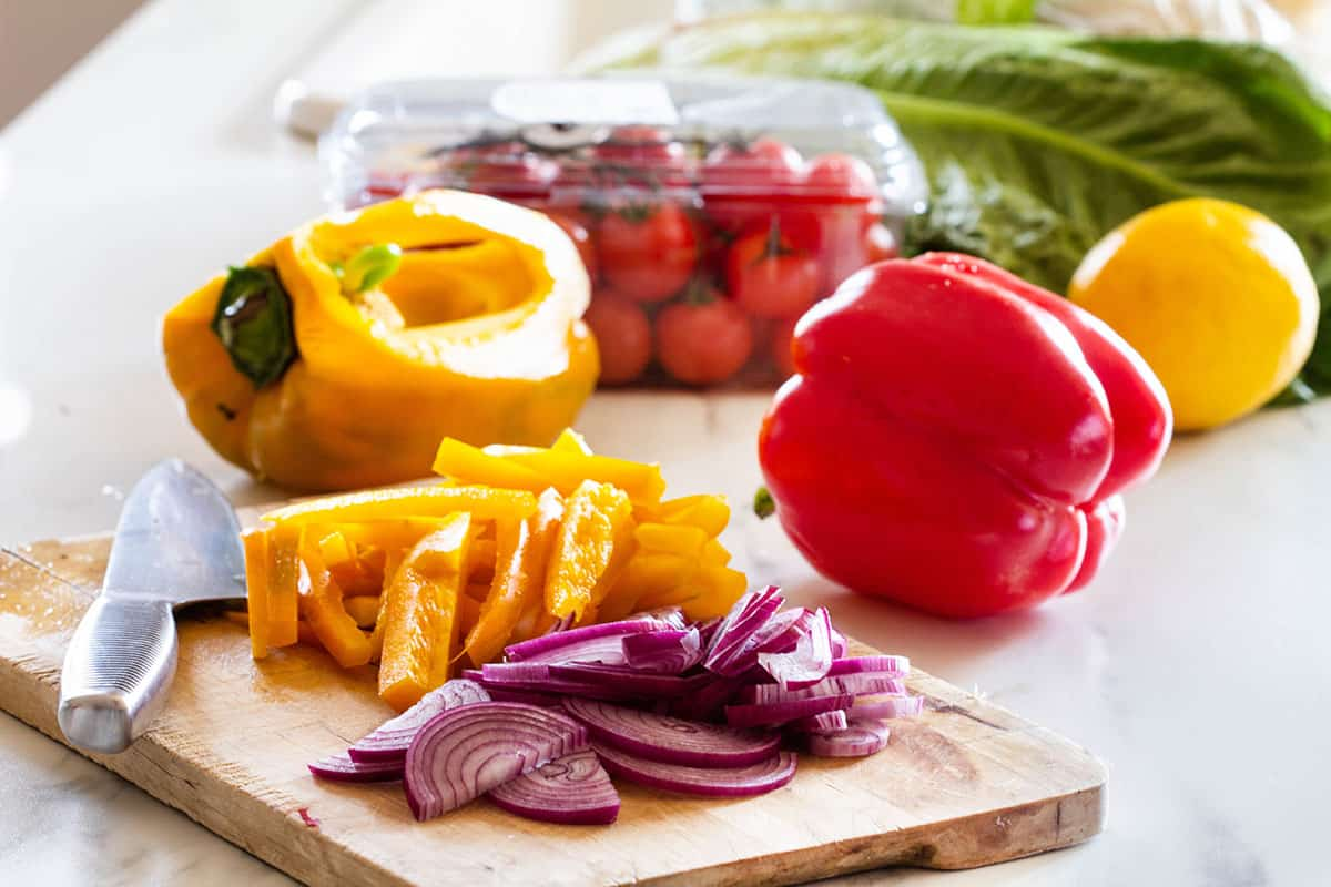 Onions and bell peppers cut on a cutting board and other vegetables needed for making Italian salad.