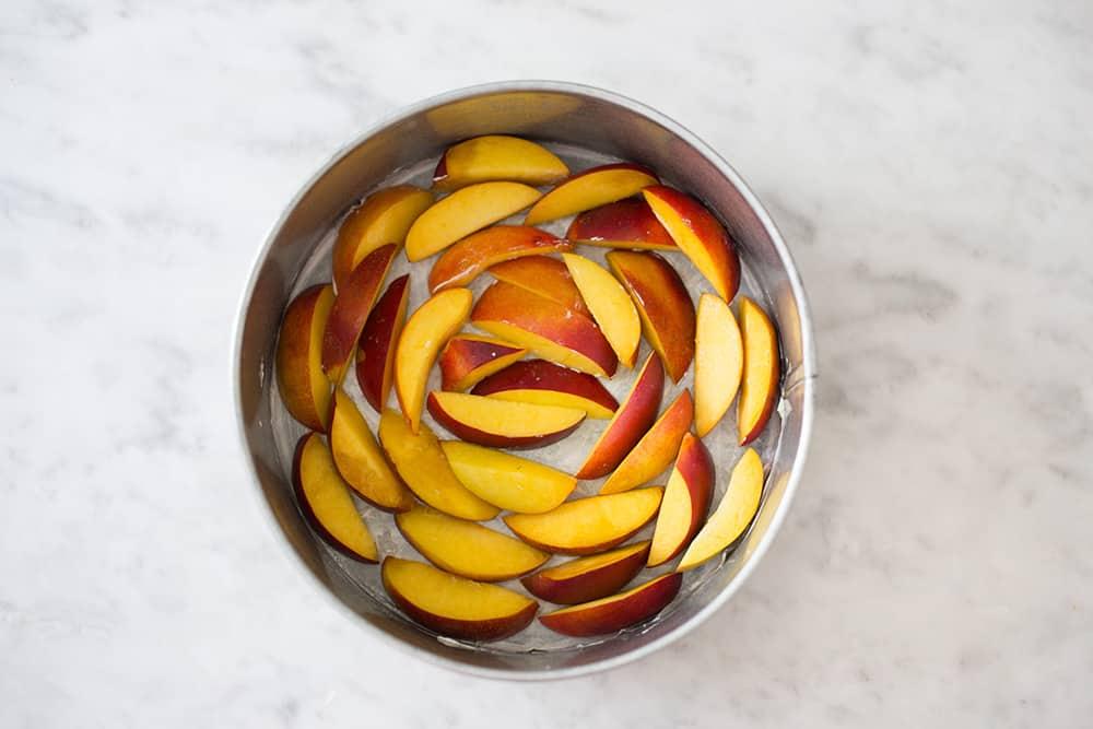 Peaches arranged on a cake pan.