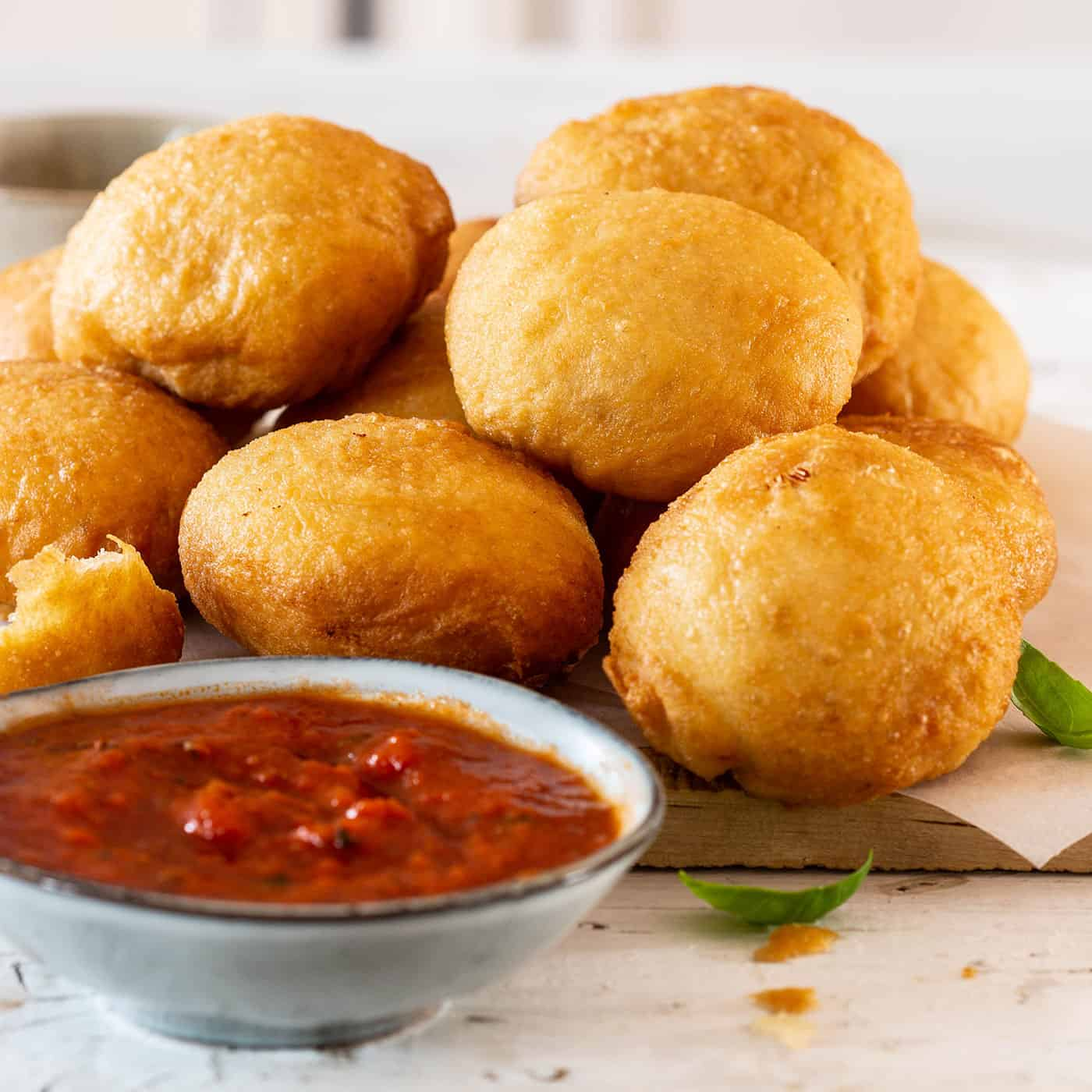 Fried pizza dough balls with tomato sauce on a board.