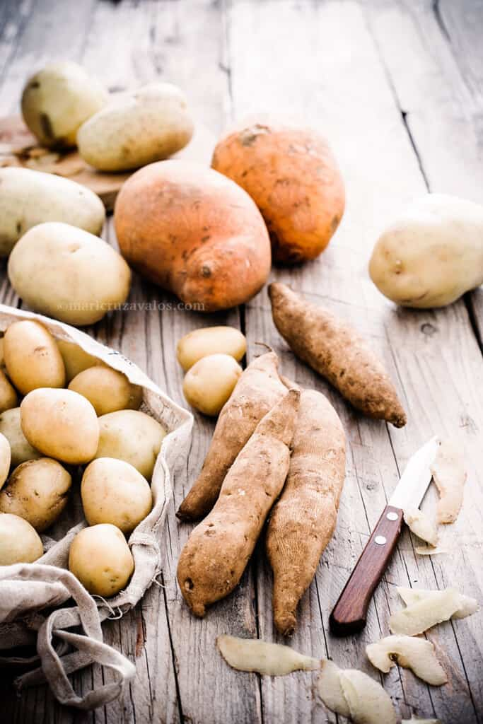 Various types of potatoes on a rustic background.
