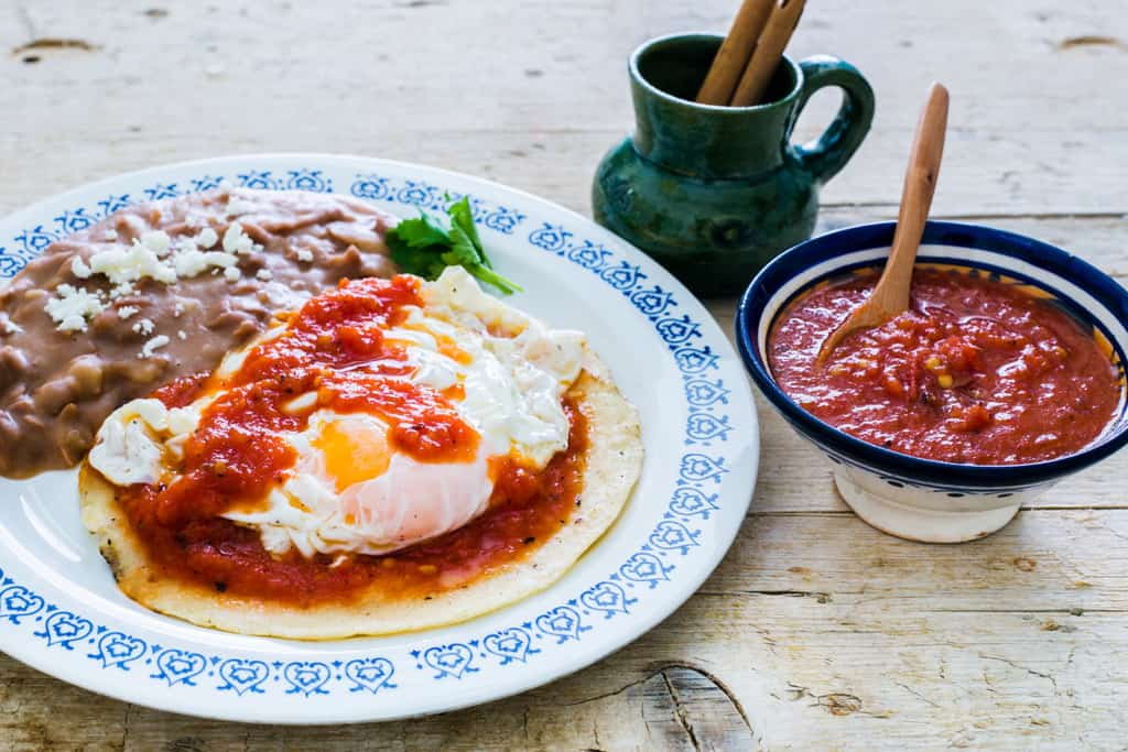 Huevos rancheros served with refried beans.
