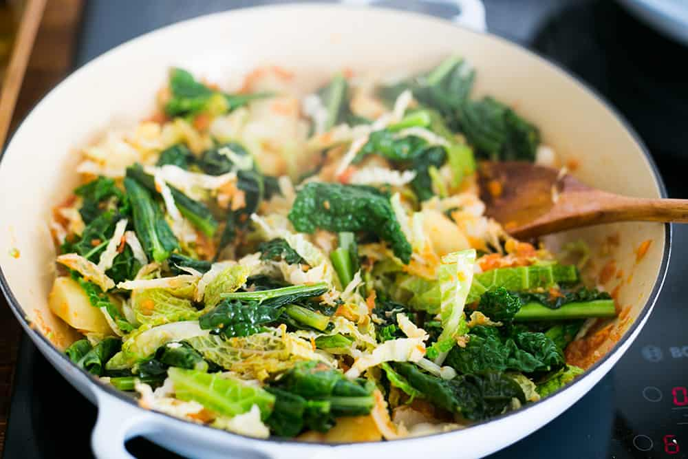 the pan with the leafy vegetables cooking.