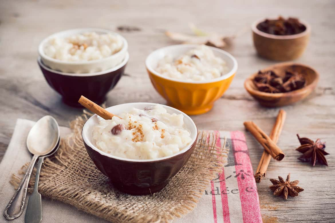 cinnamon rice pudding served in small bowls and styled for autumn with spices, dry leaves, wooded surface, etc.