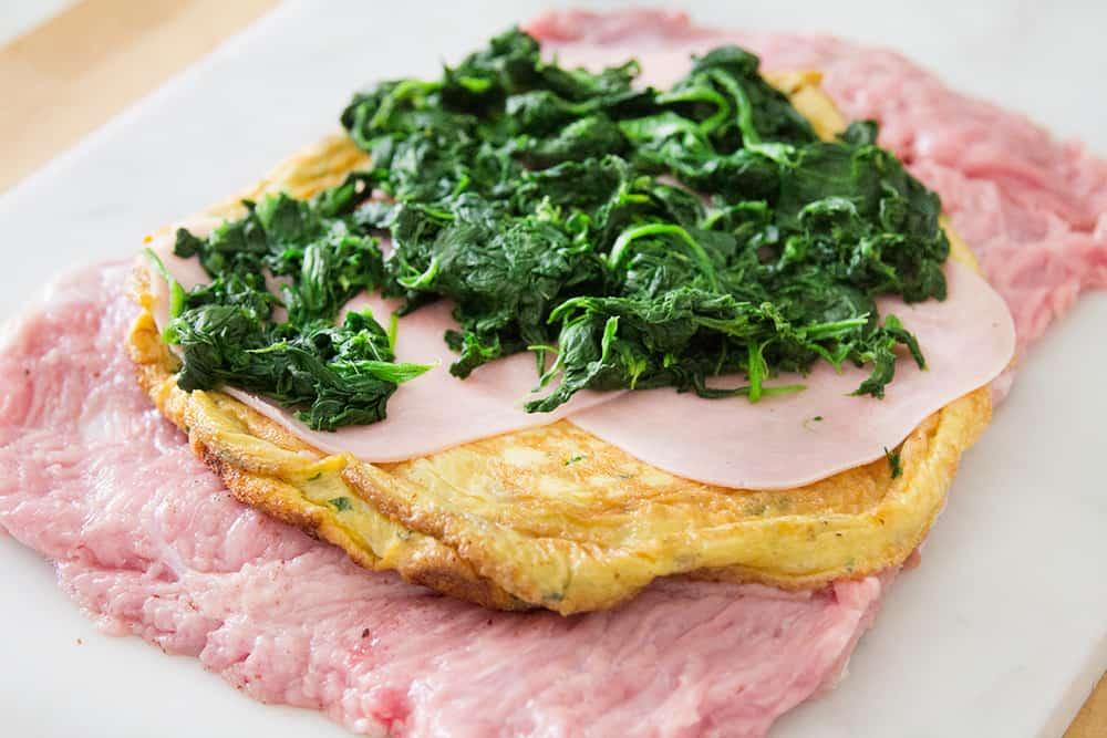 La carne extendida con encima los ingredientes del relleno: tortilla de huevos, jamón y espinacas.