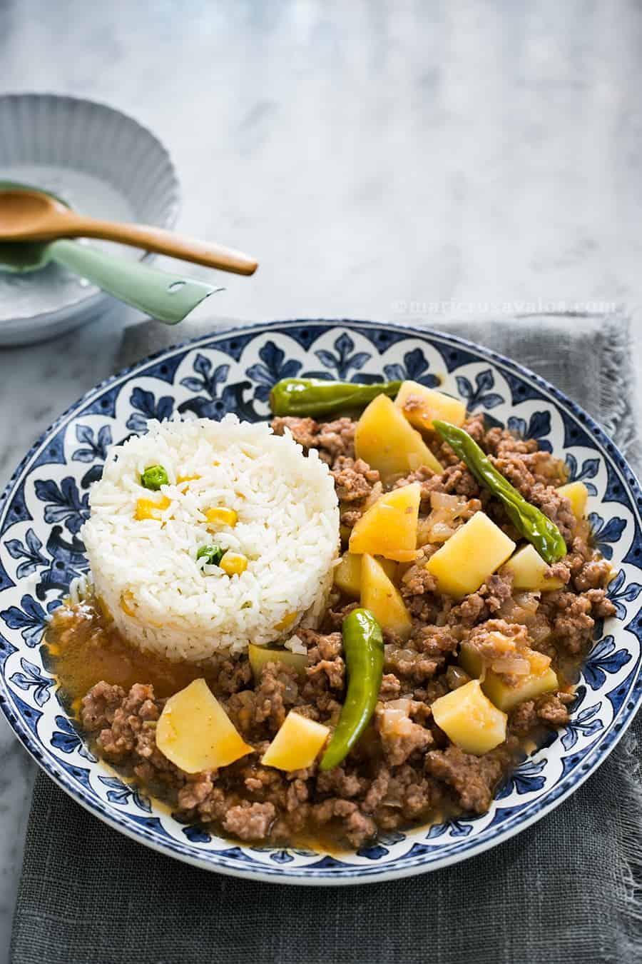 picadillo con papas acompañado de arroz blanco con elote y servido en un plato de cerámica azul y blanco.