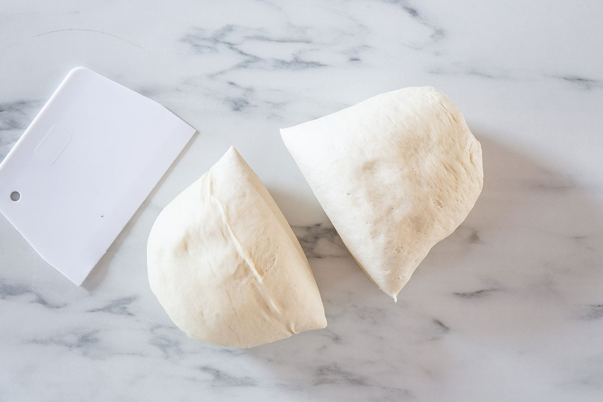 The dough divided into two equal pieces on a marble surface.