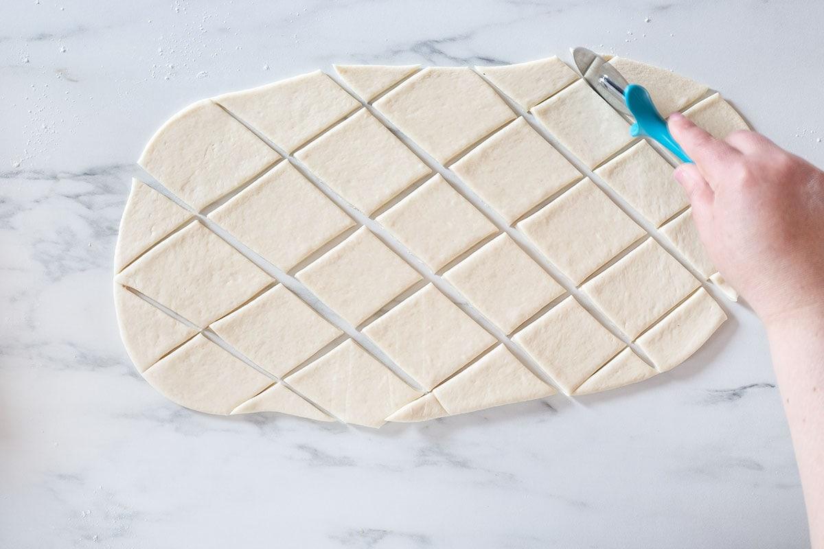 Cutting the dough into rhombus.