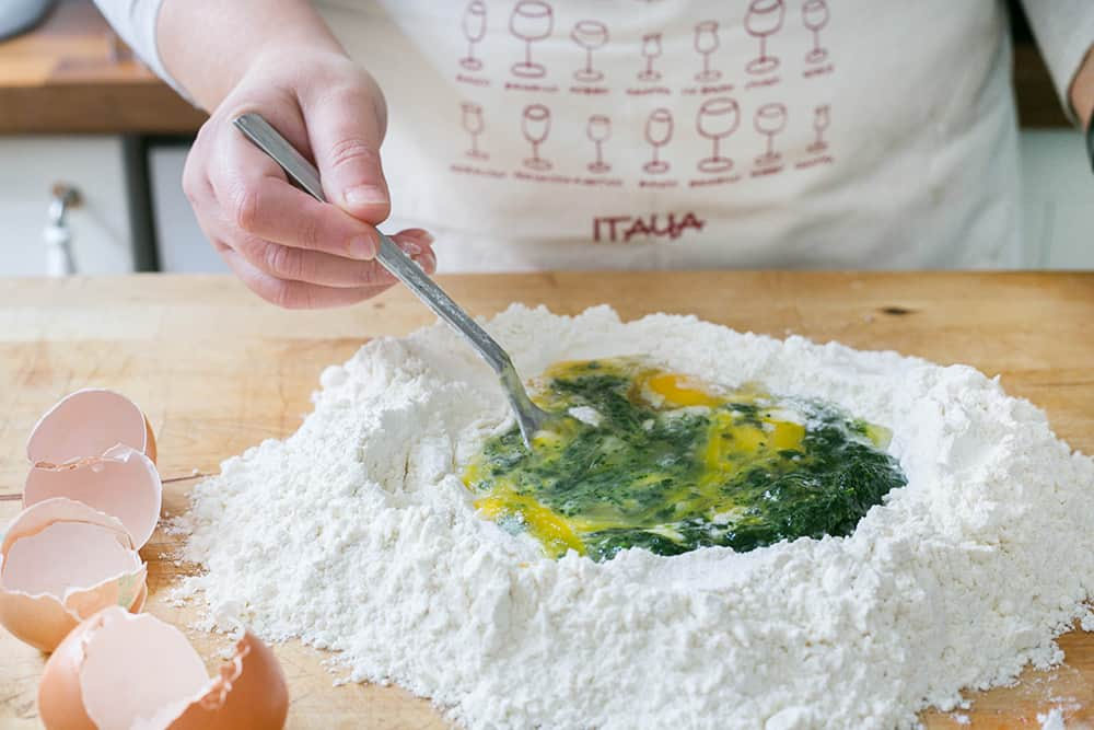 Mixing flour, eggs and spinach puree with a fork.