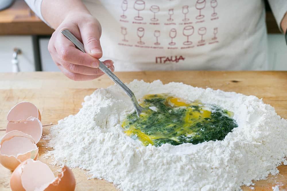Mezclando la harina con los huevos y el puré de espinacas con un tenedor.