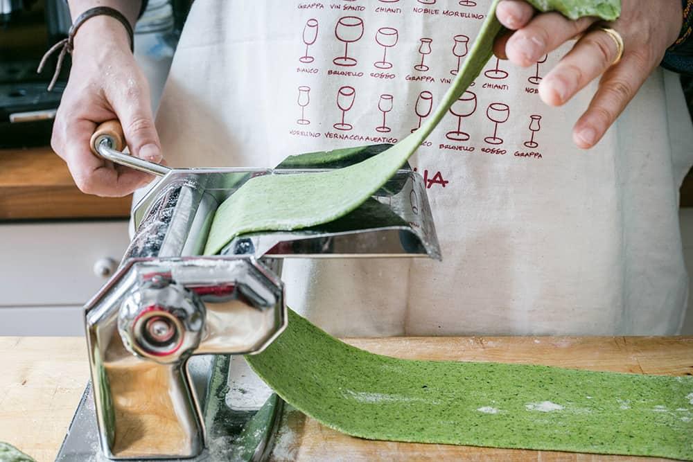 Cortando la pasta fresca verde en láminas con una máquina para pasta.