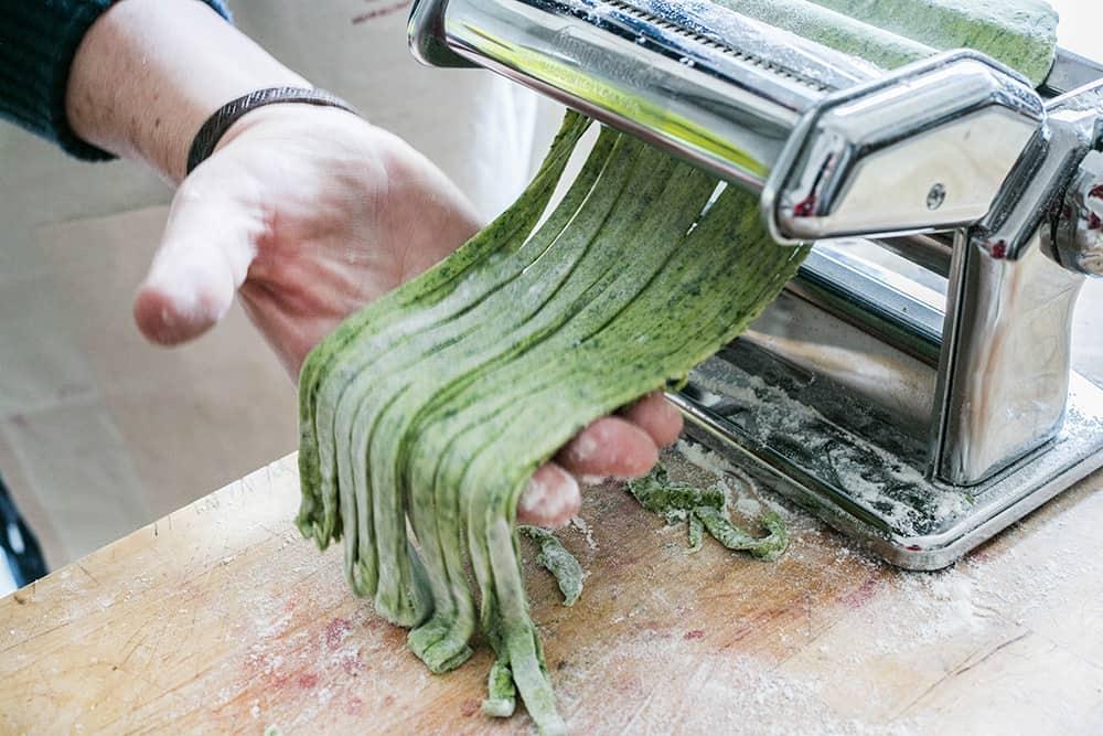 Cutting taglietelle with a pasta maker machine.