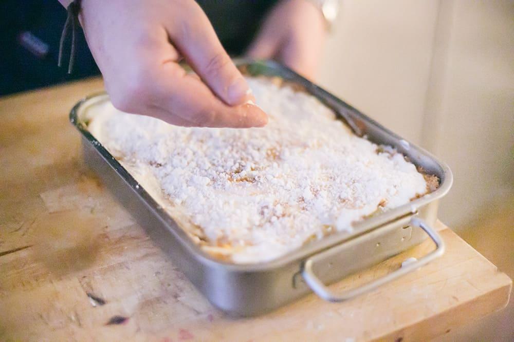 Poniendo el queso parmigiano encima de la lasaña, antes de meterla al horno.