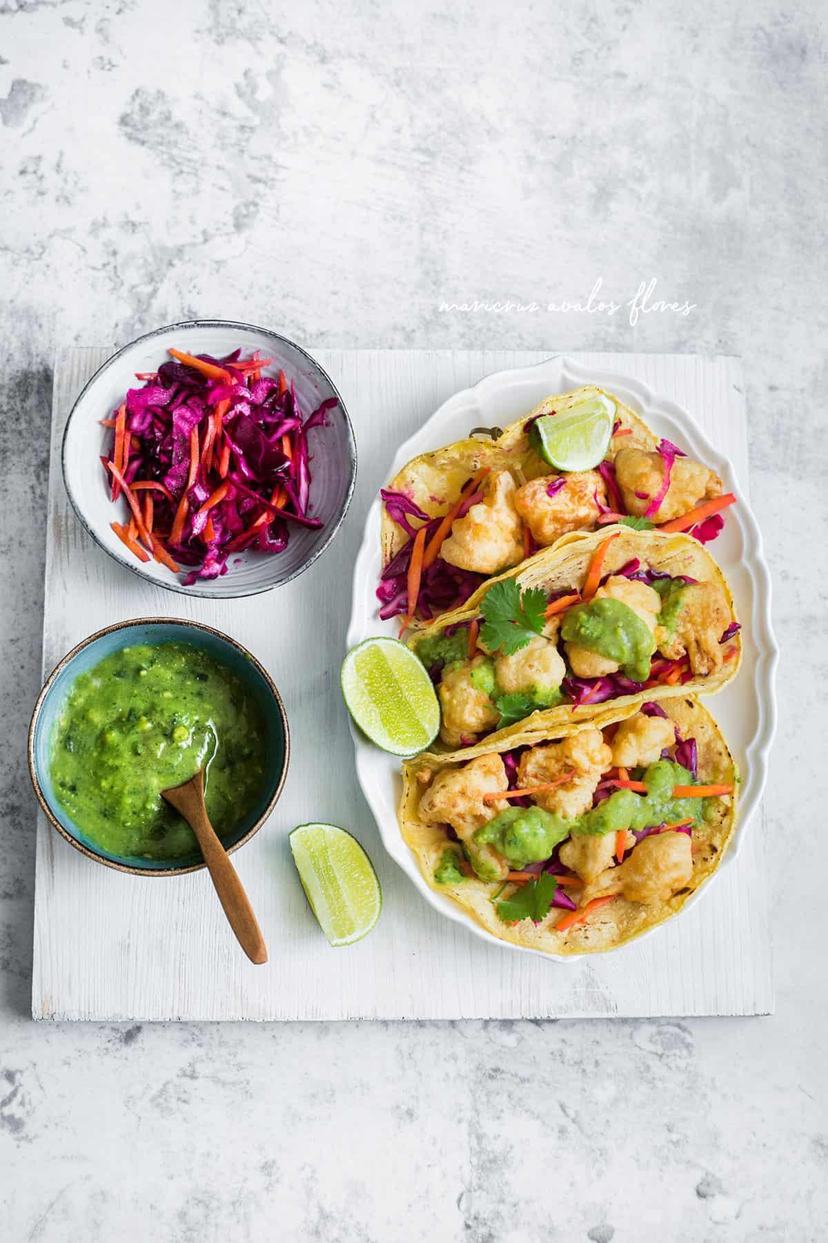 tacos de coliflor servidos con guacamole y ensalada de col morada