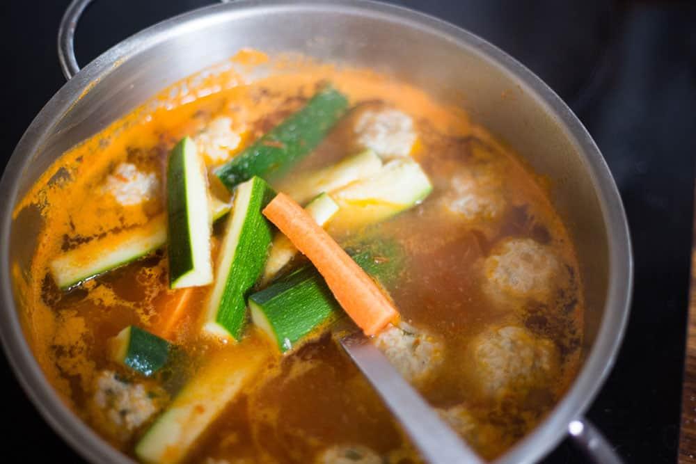 Agregando las verduras al caldo de albóndigas.