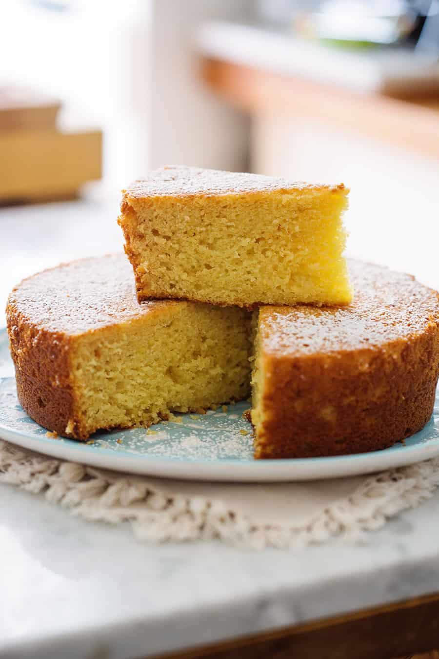 El pastel de limón y queso ricotta en un plato y con una rebanada encima.