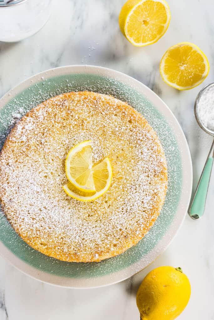 La torta di ricotta e limone intera con limoni intorno.