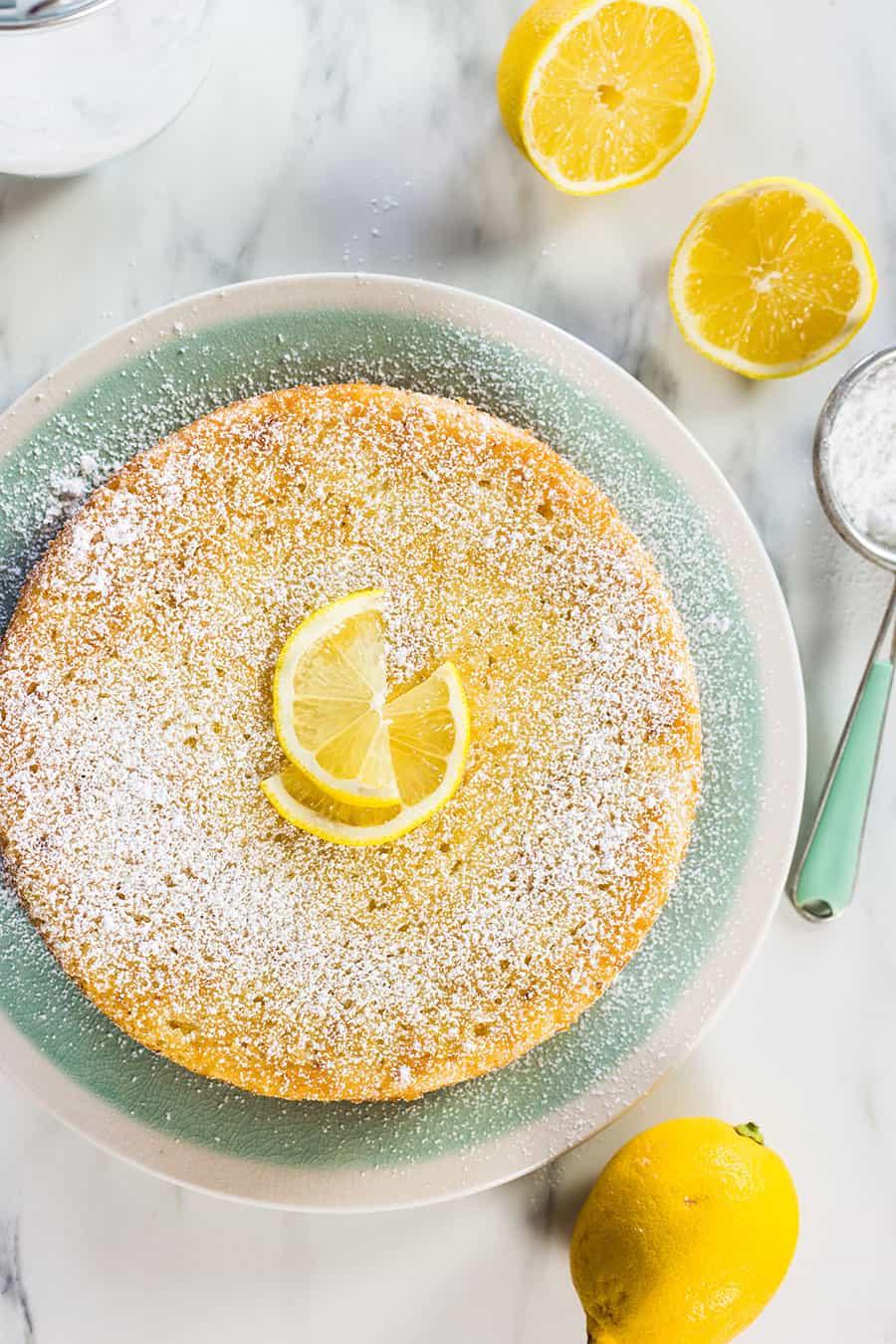 Bizcocho de ricotta y limón en un plato turquesa con limones cortados alrededor.