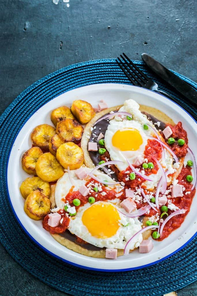 Yucatan traditional eggs served with plantains, beans, ham, peas and habanero sauce.