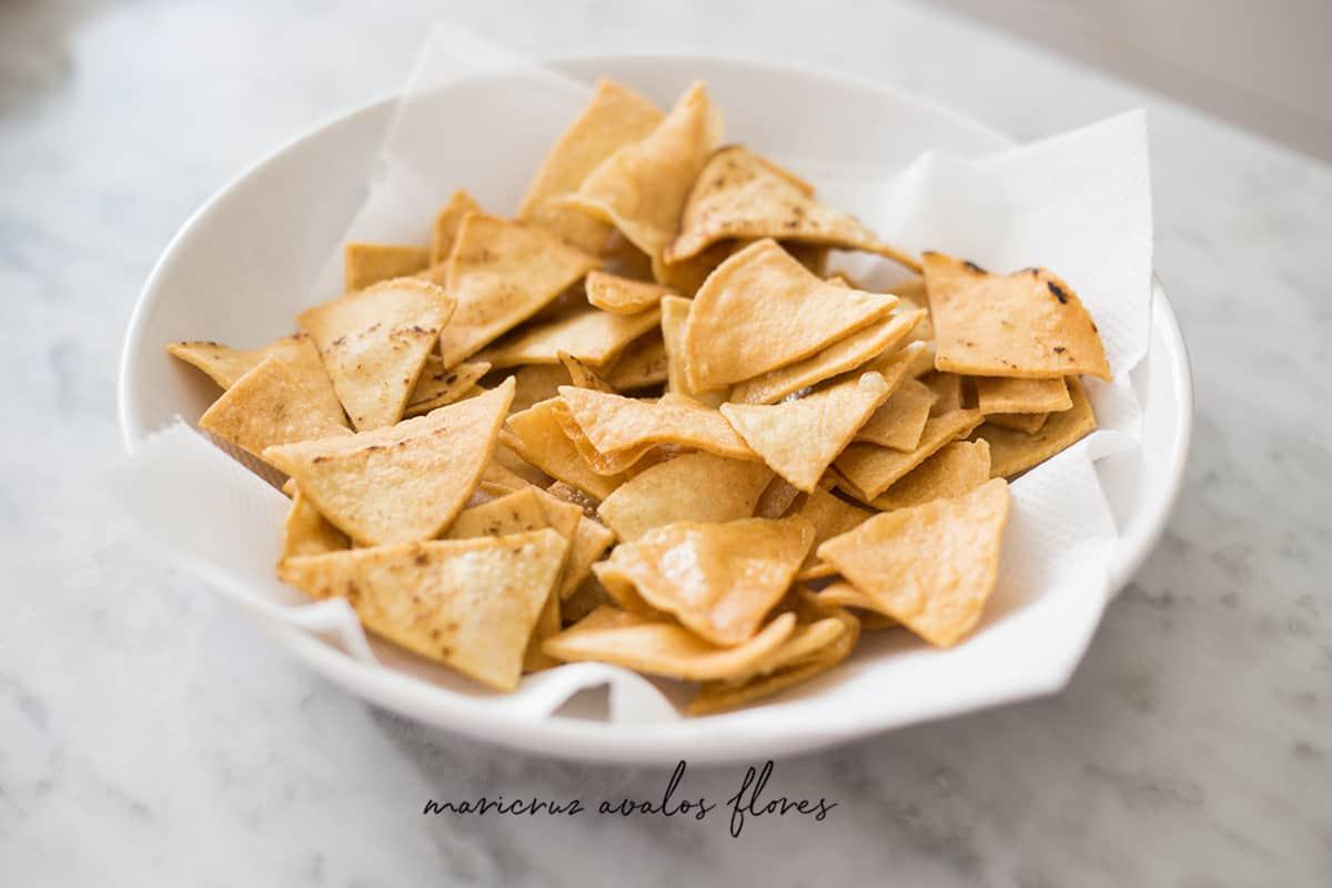 Tortillas fritas para preparar chilaquiles verdes puestas en un plato con una servilleta de papel para absorber el exceso de aceite.