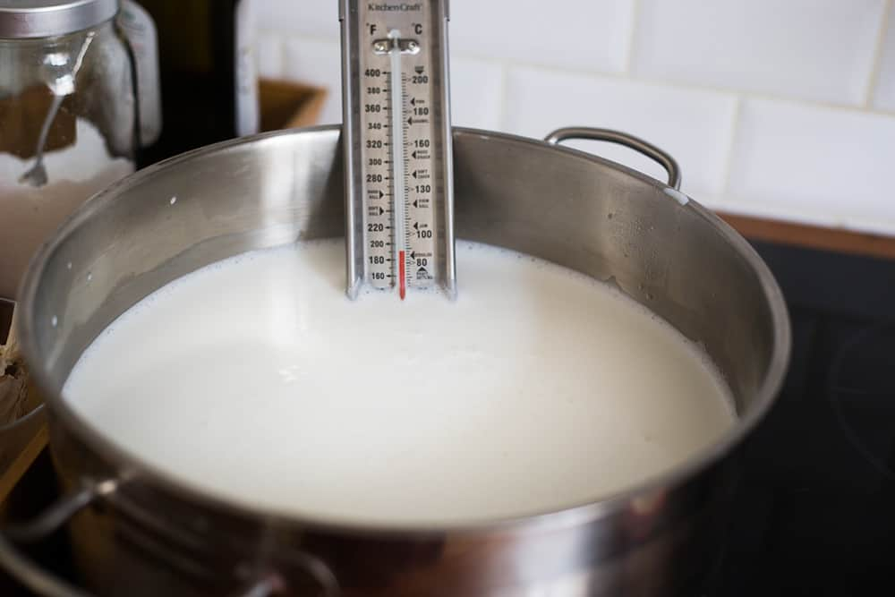Milk in a pot with a thermometer.