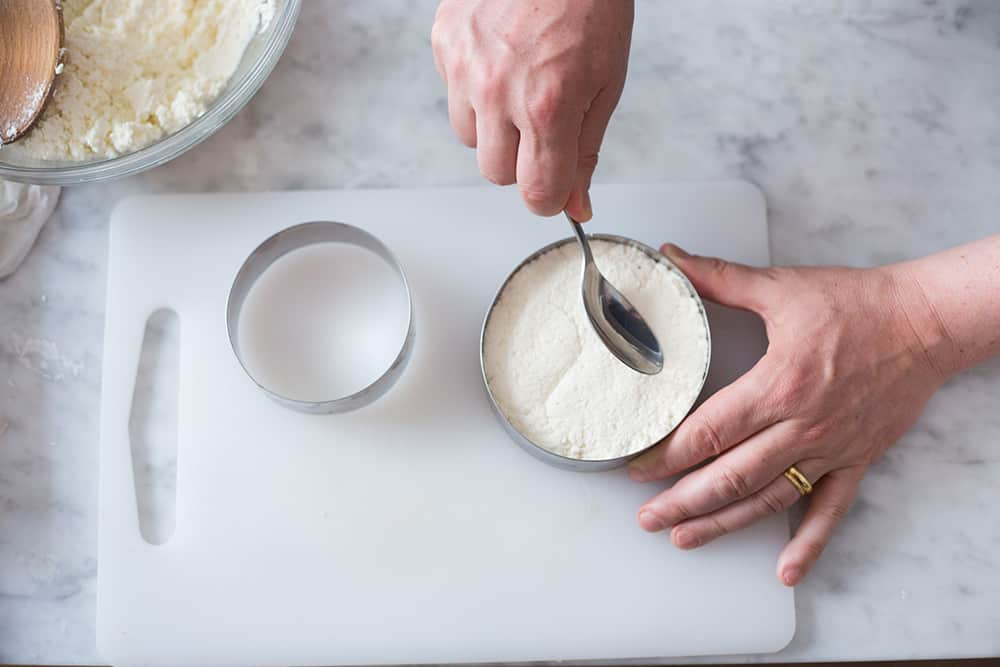 Shaping queso fresco using two cheese molds.