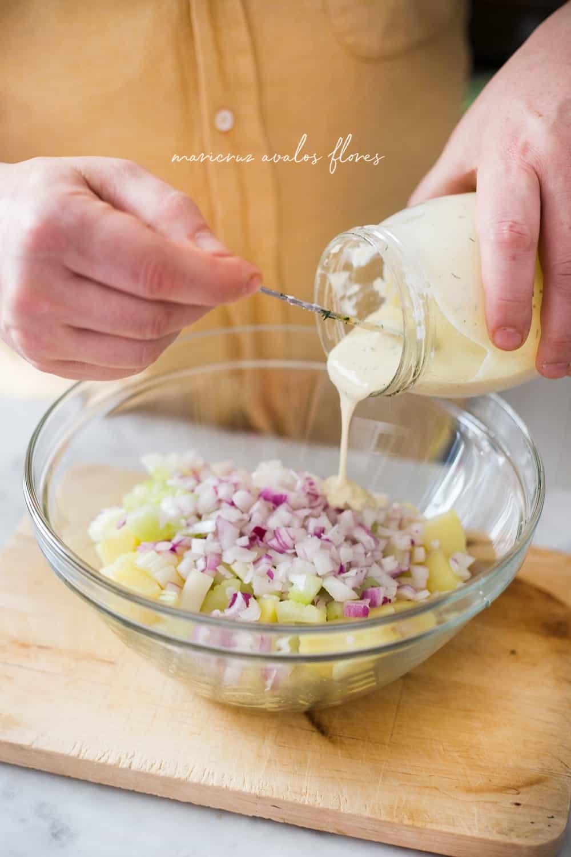 Preparando ensalada de papas sin mayonesa. Agregando el aliño ya preparado al cuenco con las papas y los demás ingredientes ya listos.