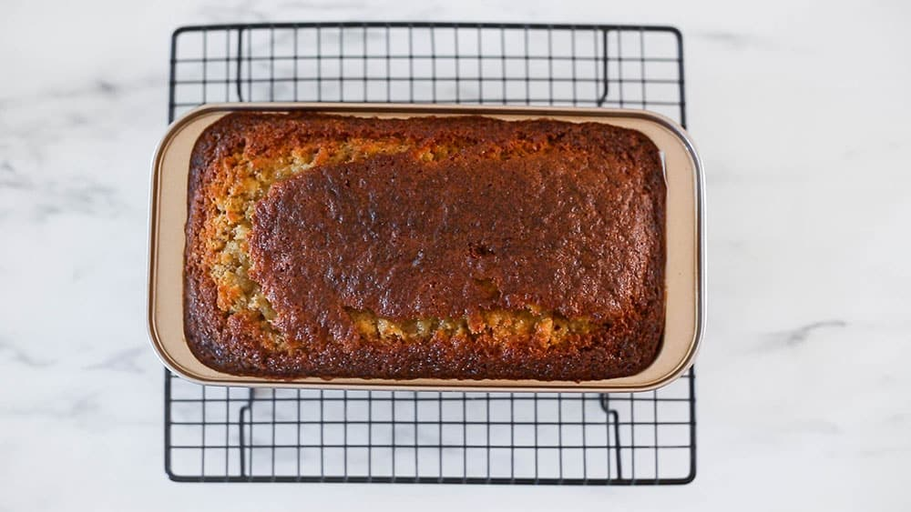 Baked chocolate chip banana bread on a cooling rack.